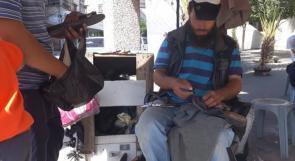 """خاص لـ""""وطن""""بالفيديو .. غزة: أبو الروس يعيل 18 نفرًا، من إصلاح الأحذية تحت شمسية مهترئة"""