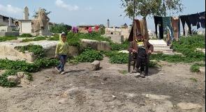 """يتخذون من القبور أسرّة لهم.. سكان مقبرة """"البرية"""" في غزة يناشدون عبر وطن لتأمين مأوى لهم"""