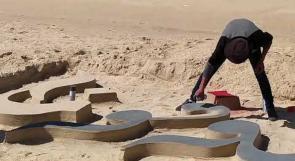 رسم شوفونا باللغتين العربية والإنجليزية على الرمال في غزة