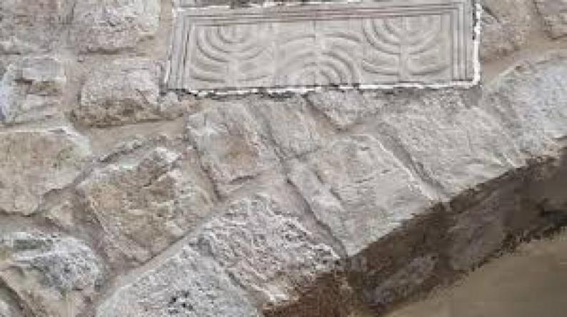 مستوطنون يثبتون حجرا يحمل كتابات عبرية في بالخليل