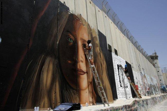 الاحتلال يرحل رسامين إيطاليين بعد اعتقالهما أثناء رسم صورة للتميمي