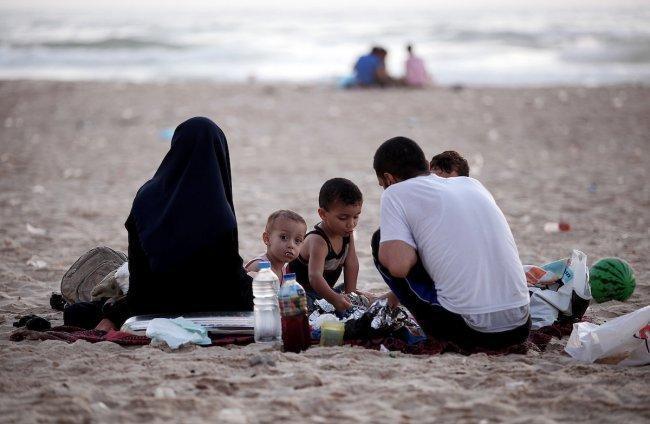 عائلة فلسطينية تتناول الافطار على شاطئ بحر غزة