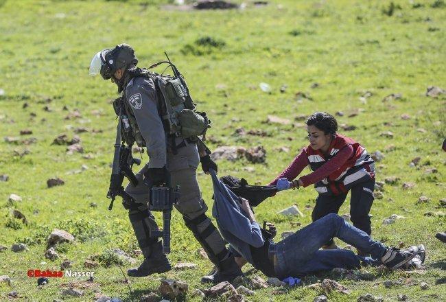 مسعفة تحاول منع جندي اسرائيلي من اعتقال مصاب خلال مواجهات عند المدخل الشمالي للبيرة