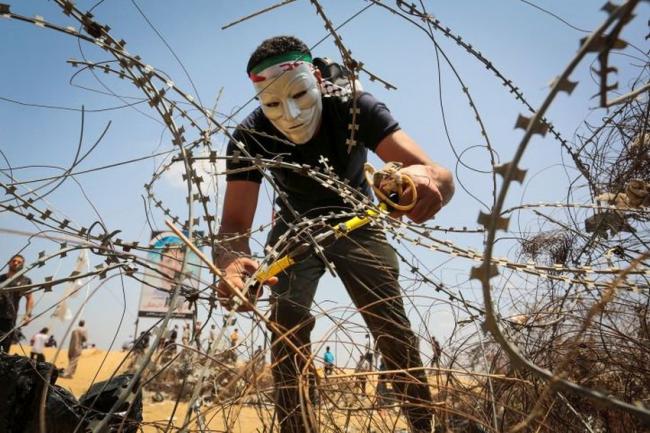 شاب يقطع السياج الفاصل على حدود قطاع غزة